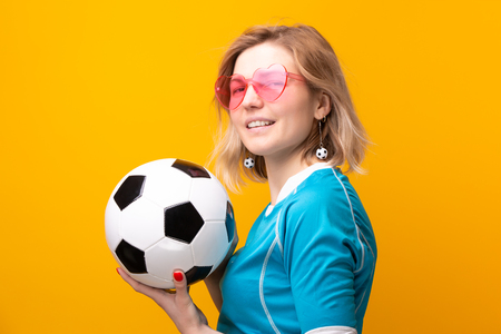 Image of blonde in pink glasses with soccer ball on orange