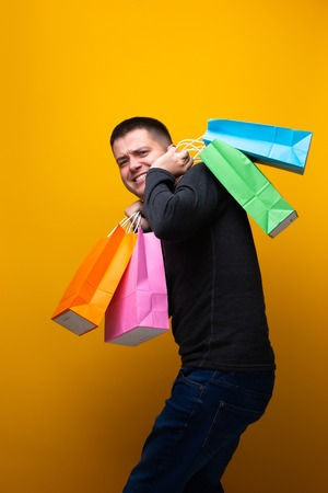 Image of happy brunet man with shopping bags on orange