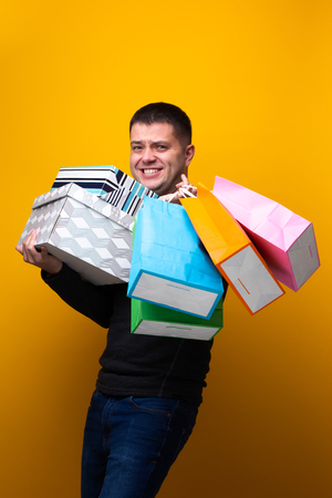Photo of male shopper with paper bags and boxes