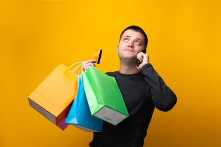 Photo of man shopper with paper bags, bank card and phone in hand