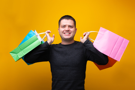 Photo of man with multi-colored shopping bags