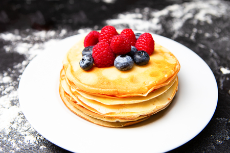 Image of plate with pancakes, blueberries, raspberries dusted with icing sugar.