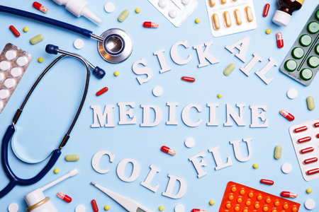 Cold medicine, thermometer, phonendoscope and words: sick, ail, medicine, cold and flu