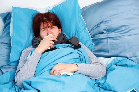 Image of sick woman lying on bed .