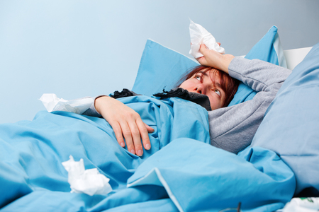 Photo of sick woman with paper handkerchiefs lying on bed