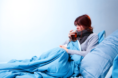 Photo of sick brunette with cup of tea sitting in bed.