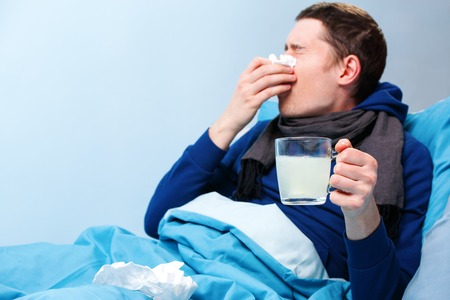 Photo of sick man in scarf with cup of medicine lying in bed Banco de Imagens - 120464721