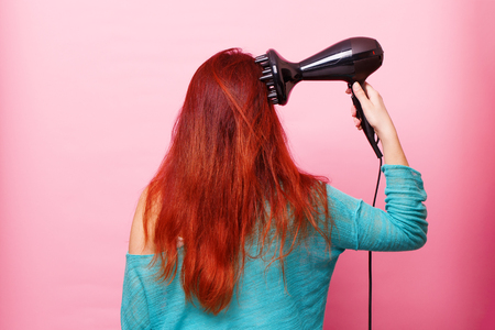 Woman holding a hairdryer on a pink background
