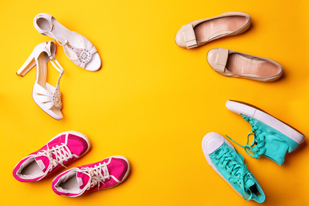 Collection of womens shoes on yellow background