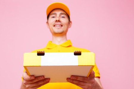 Photo of courier man with pizza box in hands . Stock Photo