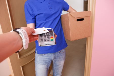 Woman pays for delivery credit card to courier via pin pad.