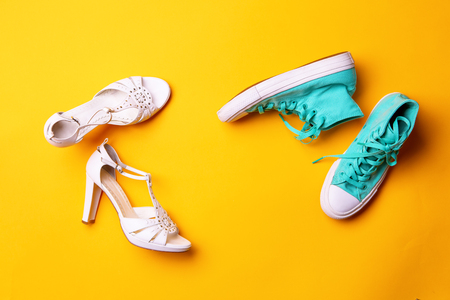 A pair of white high-heeled sandals and a pair of turquoise sneakers on yellow background