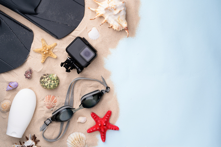 Swimming goggles, flippers, sunscreen and action camera on the sand with shells and starfishes.