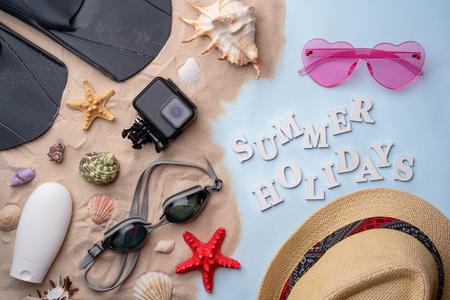 Swimming goggles, flippers, flip-flops, sunglasses, hat, sunscreen and action camera on sand
