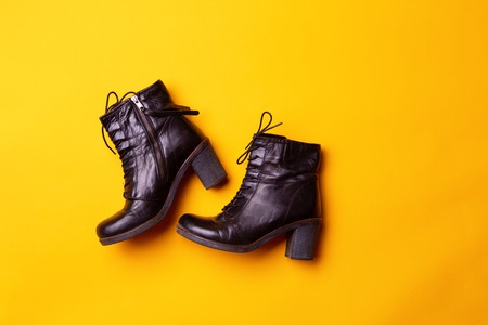Elegant women black heeled boots. Top view of black boots on a yellow background. Stock Photo