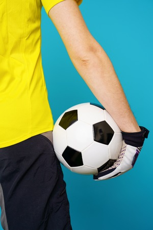 Man is socccer fan in yellow t-shirt with soccer ball Stock Photo