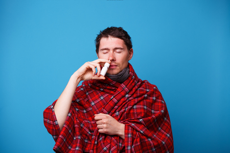 A wrapped in a blanket sick man is standing and using nasal spray