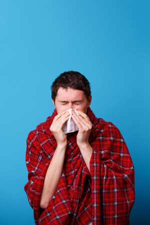 A wrapped in a blanket sick man is blowing his nose in white handkerchief