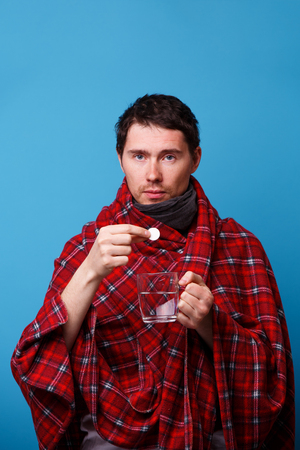 A wrapped in a blanket sick man with tablet and mug.