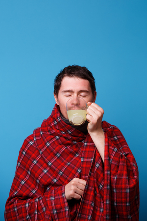 A wrapped in a blanket sick man is drinking from cup of medicine. Standard-Bild - 122705346
