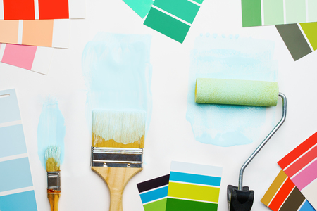 Picture of palette with blue and green colors, roller, brushes