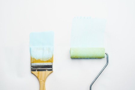 Photo of brush and roller with blue paint