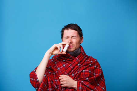 A wrapped in a blanket sick man is standing and using nasal spray Foto de archivo