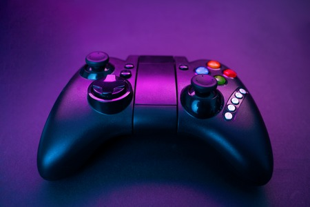 Gamepad on violet table background.