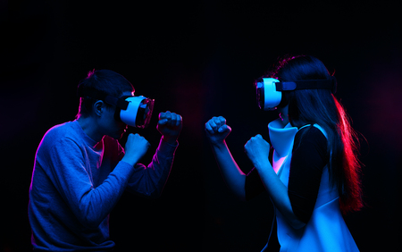Couple with virtual reality headset are playing game and fighting. Banco de Imagens