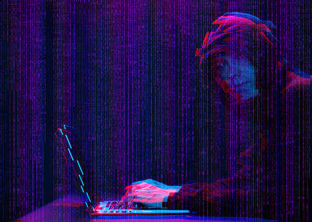 Hacker working with laptop in dark room with digital interface around. Image with glitch effect. Banco de Imagens