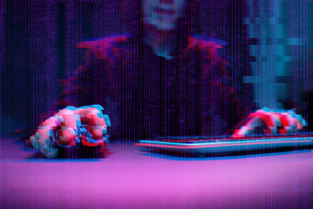 Hacker working with computer in dark room with digital interface around. Image with glitch effect.