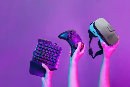 Set of hands with gamepad, keyboard, virtual reality headset and headphones on violet background.