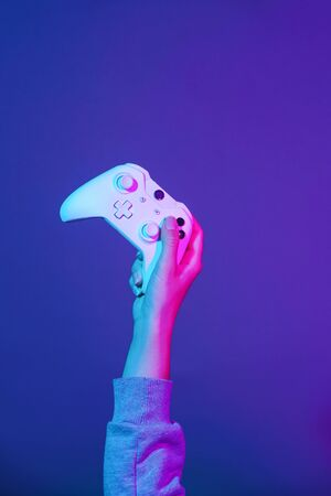 Hand with white gamepad on dark violet background.