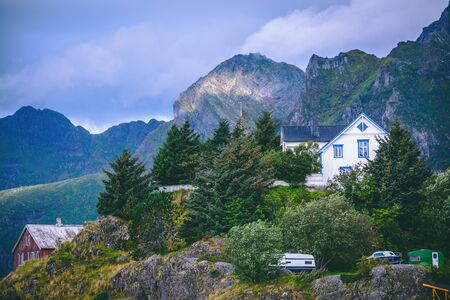 Photo of picturesque mountainous area with vegetation, houses, cloudy sky in Norway on summer