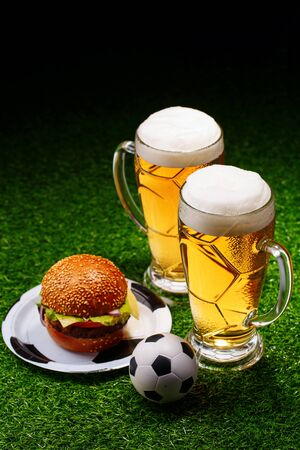Two glasses of beer, hamburger and soccer ball on green grass.