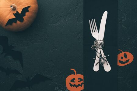 Photo of halloween pumpkin, knife, fork, plate, bat .