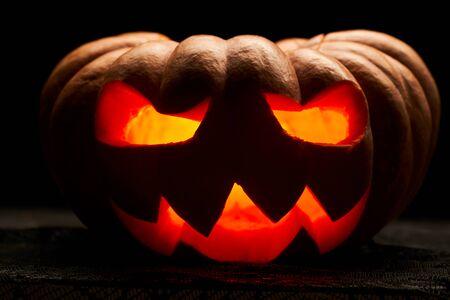 Nahaufnahme Foto von einem Halloween-Kürbis mit brennenden Mündern auf leerem schwarzem Hintergrund Standard-Bild
