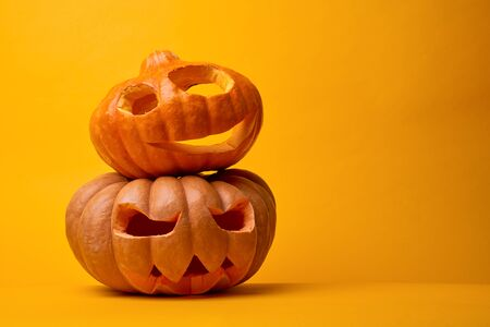 Photo of two halloween pumpkins on empty orange background Foto de archivo