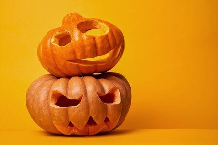 Photo of two halloween pumpkins on empty orange background