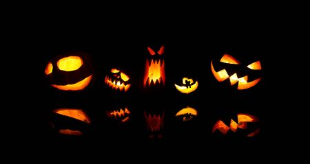 Image of halloween pumpkins with burning mouths on blank black background. Imagens