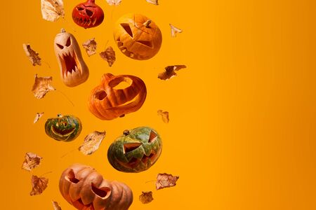 Several flying scary halloween pumpkins and dry leaves on empty orange background