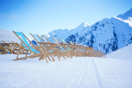 Sun loungers against backdrop of mountains at winter resort