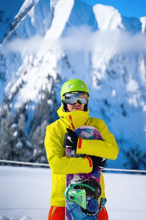 Photo of sportive man with snowboard against background of mountains