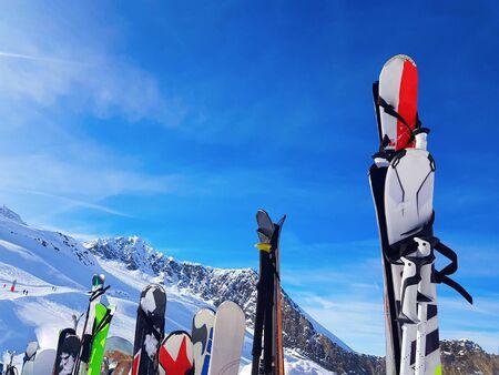 Immagine di sci e snowboard multicolori nella neve al resort invernale nel pomeriggio.