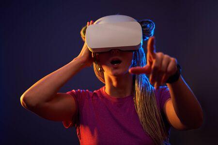 Frau verwendet Virtual-Reality-Headset. Studioportrait mit Neonlicht.
