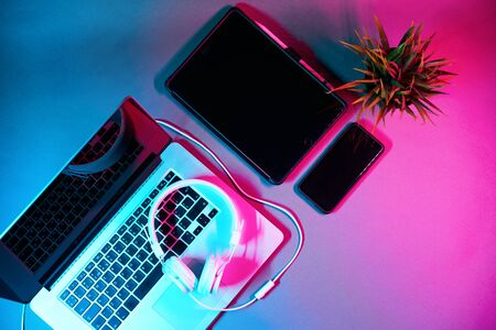 Laptop with headphones, tablet, phone and green flower on the table in modern neon colors. 写真素材 - 136371454