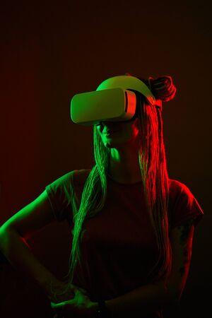 Woman is using virtual reality headset. Neon light studio portrait.