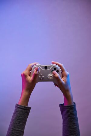 Female hands with a game joystick on violet background.