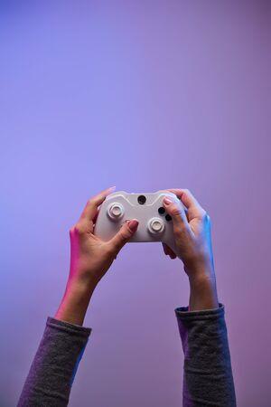Female hands with a game joystick on violet background. Gamer concept. 写真素材