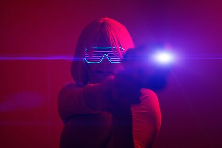 Girl with blaster in the futuristic battle. Concept virtual reality, cyber game.